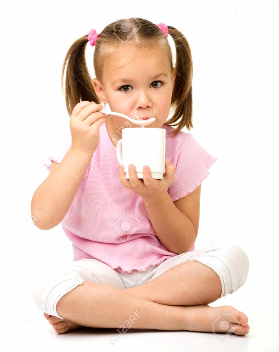 photo schattig klein meisje is het eten van yoghurt van de beker met lepel zittend op de vloer geƒ ¯ solee iwpor
